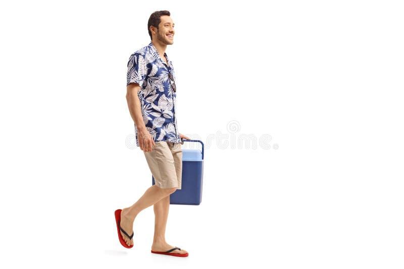 Junger Mann, der einen Kühlkasten und ein Gehen hält stockfoto