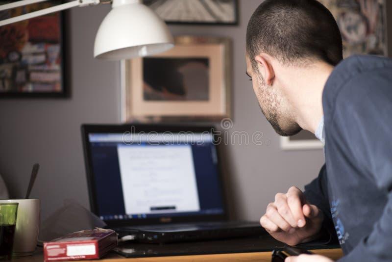 Junger Mann, der einen Laptop in seinem Studienraum verwendet lizenzfreie stockbilder