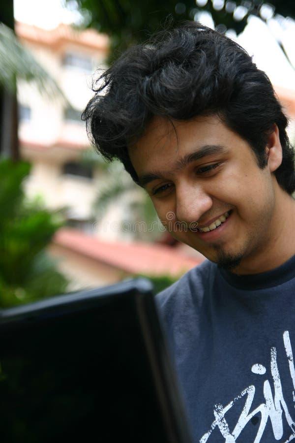 Junger Mann, der einen Laptop verwendet lizenzfreie stockbilder