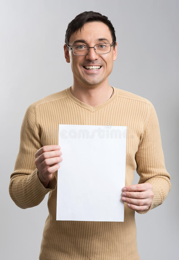 Junger Mann, der einen Leerbeleg hält stockbild