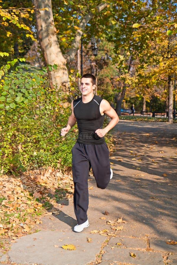 Junger Mann, der in einen schönen Park läuft stockbild