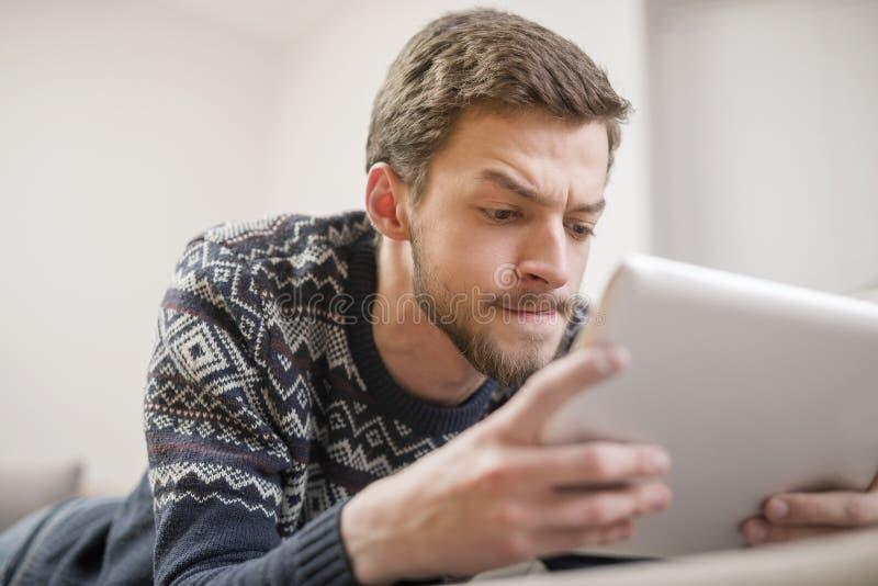 Junger Mann, der einen Tablet-Computer beim Lügen auf der Couch betrachtet stockbild