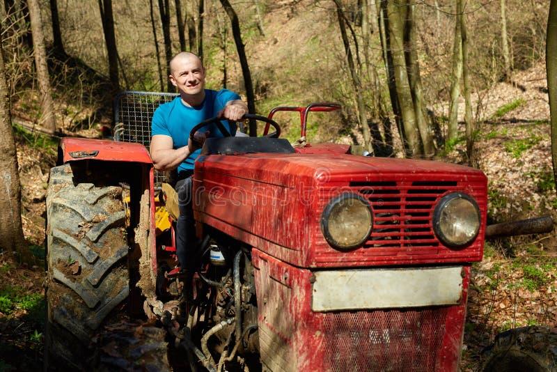 Junger Mann, der einen Traktor in einem Wald fährt stockfoto