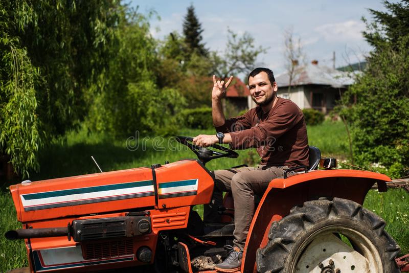 Junger Mann, der einen Traktor fährt lizenzfreies stockbild