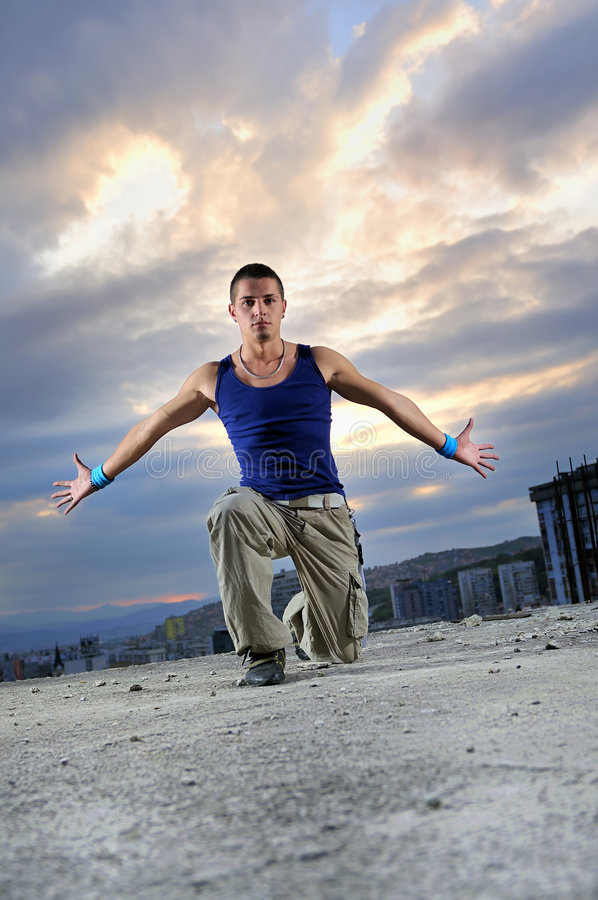 Junger Mann, der in einer Luft im Freien nachts springt stockfotografie
