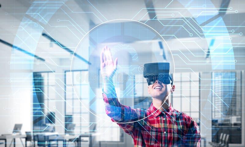 Junger Mann in der erfahrenden Innentechnologie der virtuellen Realität des modernen Büros lizenzfreies stockfoto