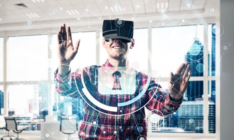 Junger Mann in der erfahrenden Innenvirtuellen Realität des modernen Büros stockfoto