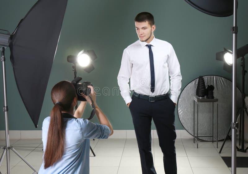 Junger Mann, der für Berufsfotografen aufwirft lizenzfreie stockbilder
