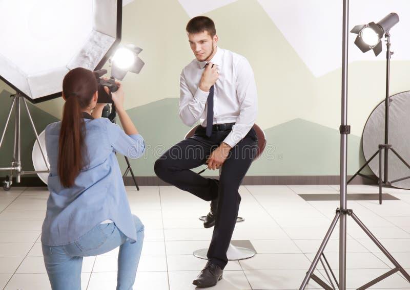 Junger Mann, der für Berufsfotografen aufwirft stockbild