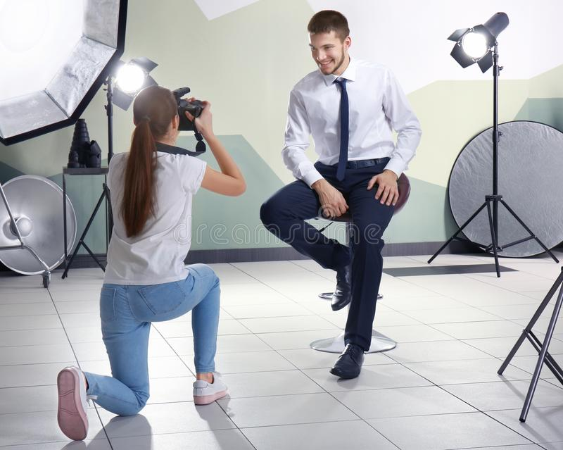 Junger Mann, der für Berufsfotografen aufwirft stockfotografie