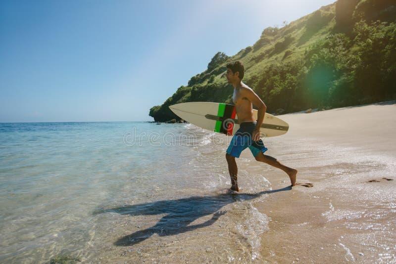 Junger Mann, der für das Wasser surft in das Meer geht lizenzfreies stockbild