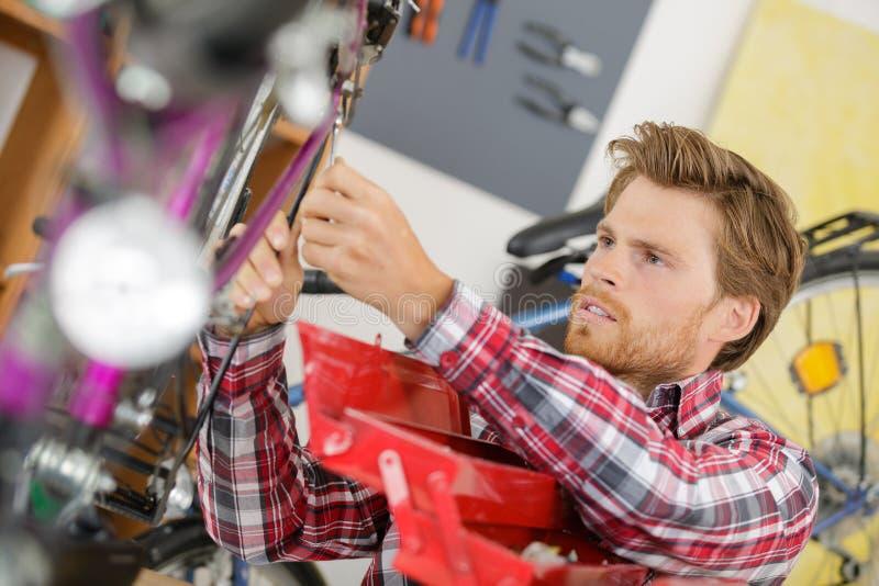 Junger Mann, der Fahrradhinterrad repariert lizenzfreies stockfoto