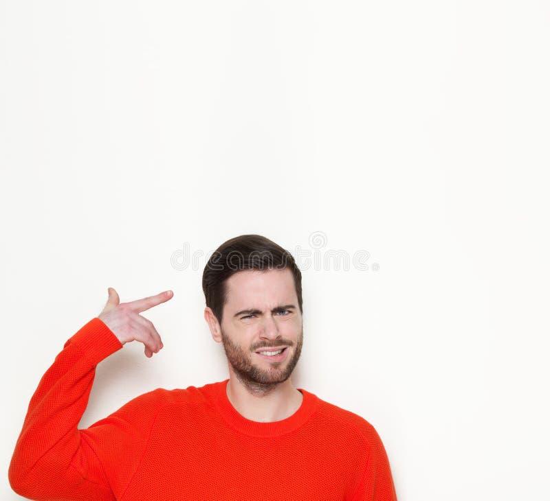 Junger Mann, der Finger auf Kopf zeigt stockbilder