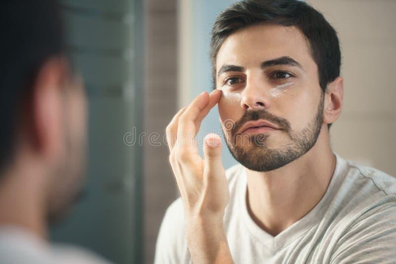 Junger Mann, der fot Hautpflege der Antialternlotion anwendet lizenzfreie stockfotografie