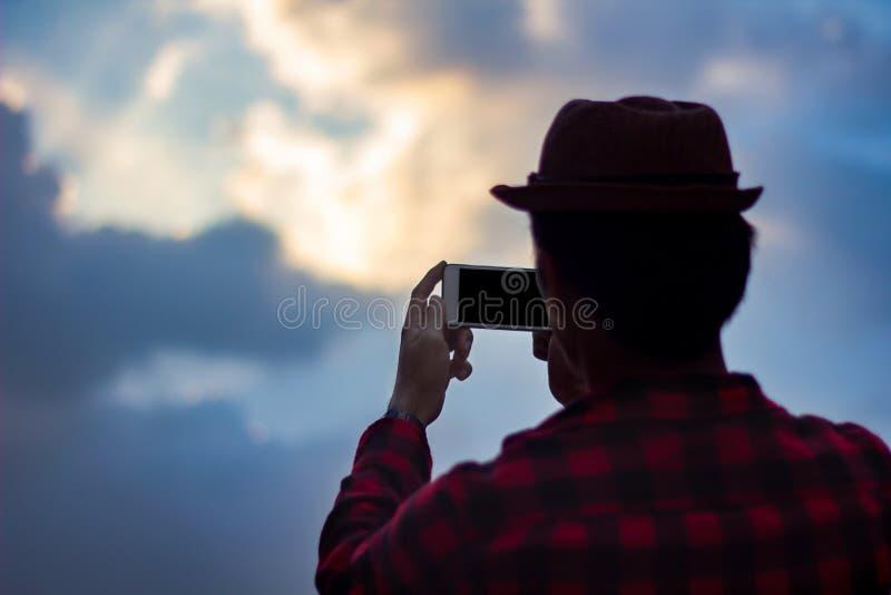 Junger Mann, der Foto des schönen blauen Himmels mit beweglichem intelligentem p macht lizenzfreie stockfotografie