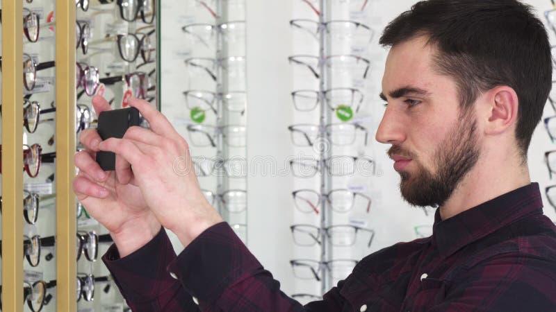 Junger Mann, der Fotos von Gläsern am Eyewearspeicher macht stockfotos