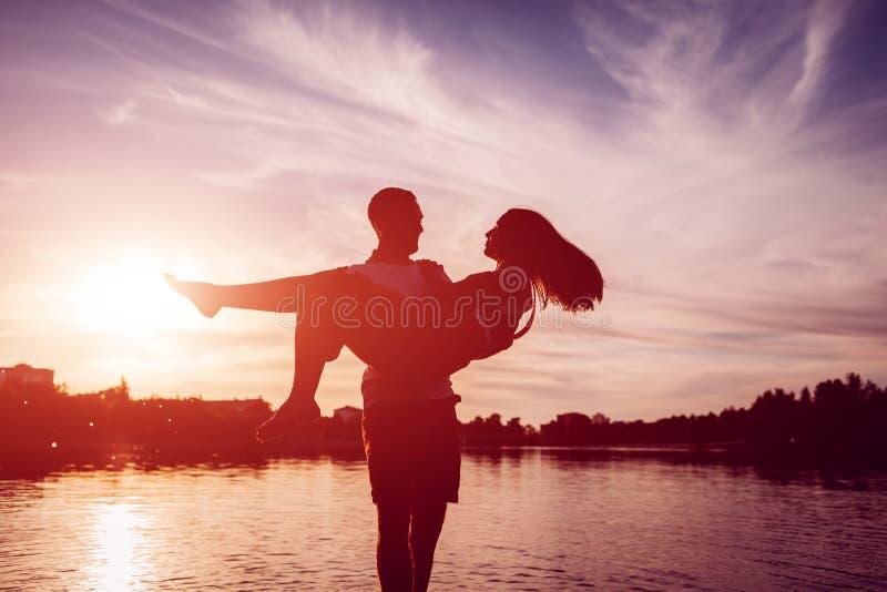 Junger Mann, der Frau auf Sommerflussbank hält Paare, die Spaß bei Sonnenuntergang haben Kerlkühlen lizenzfreie stockfotos