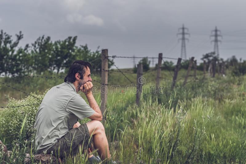 Junger Mann in der Freizeitbekleidung, die in der Landschaft sitzt stockfotografie