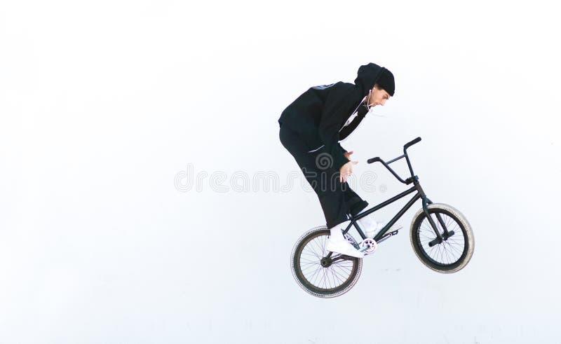 Junger Mann in der Freizeitbekleidung macht Tricks auf bmx vor dem hintergrund einer weißen Wand stockfotos
