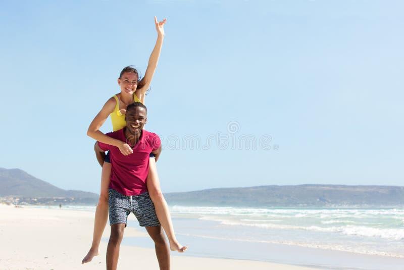 Junger Mann, der Freundin am Strand huckepack trägt lizenzfreie stockfotos