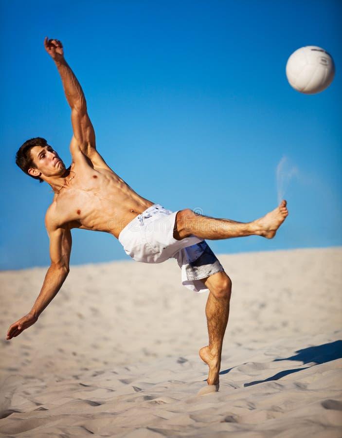 Junger Mann, der Fußball spielt stockfoto