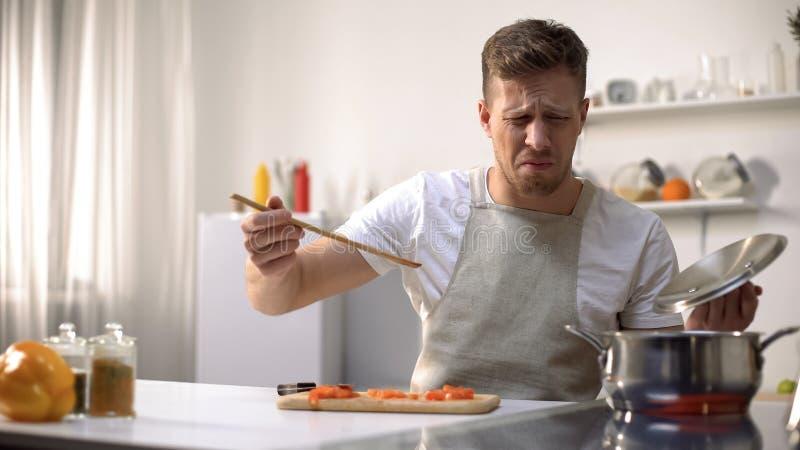 Junger Mann, der gekochtes Essen mit angewidertem Gesichtsausdruck, lustiges Gesichtes Verziehen Gesichtes Verziehen schmeckt stockfotografie