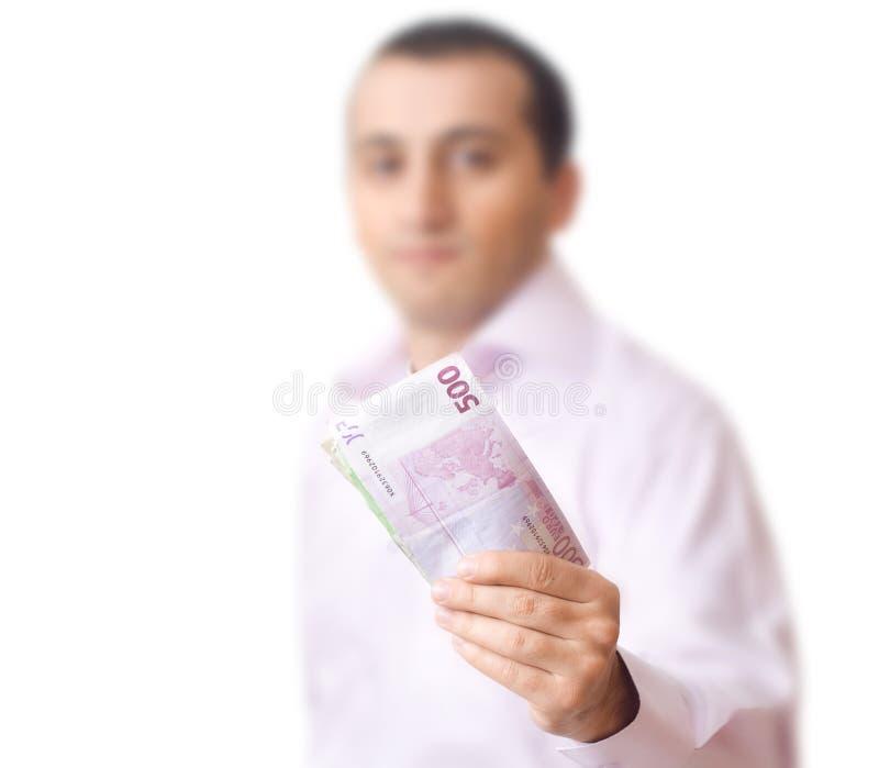 Junger Mann, der Geld zeigt stockbild
