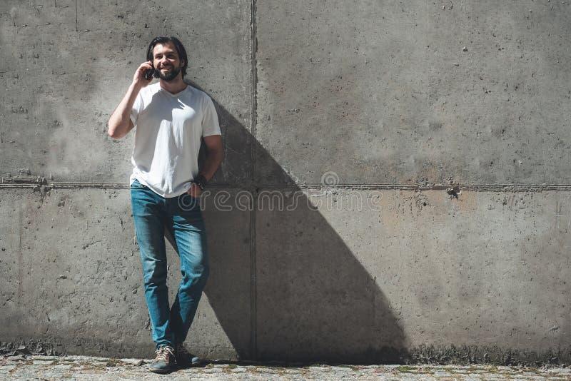 Junger Mann, der Gerät auf der Straße für Kommunikation verwendet lizenzfreie stockfotografie