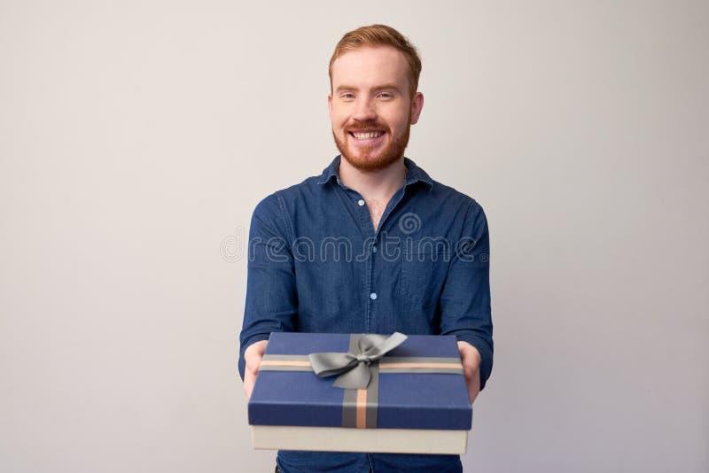 Junger Mann, der Geschenk gibt lizenzfreies stockfoto