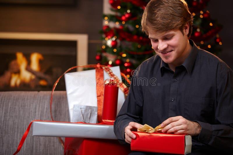 Junger Mann, der Geschenke am Weihnachten einwickelt stockbilder