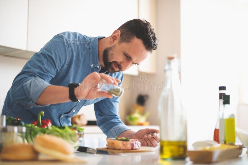 Junger Mann, der Gewürze Fleisch bei der Stellung nahe Küchentisch hinzufügt stockfotos