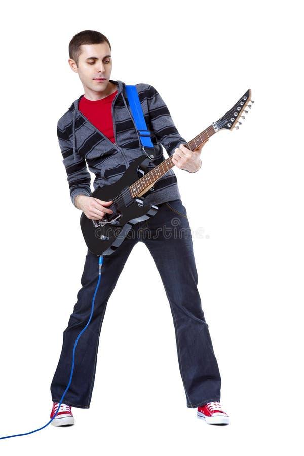 Junger Mann, der Gitarre über weißem Hintergrund spielt stockbild