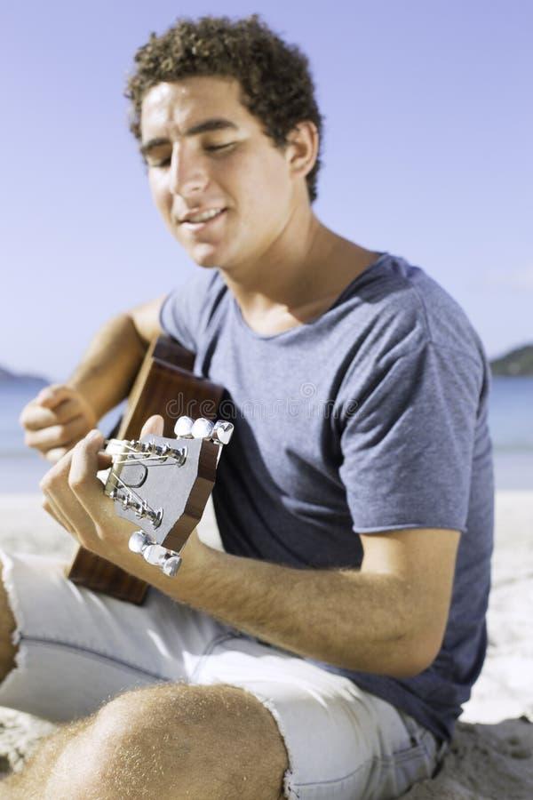Junger Mann, der Gitarre auf dem Strand spielt stockfotografie