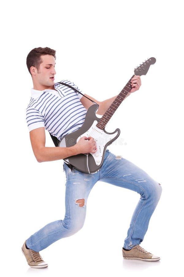 Junger Mann, der Gitarre spielt stockfotografie