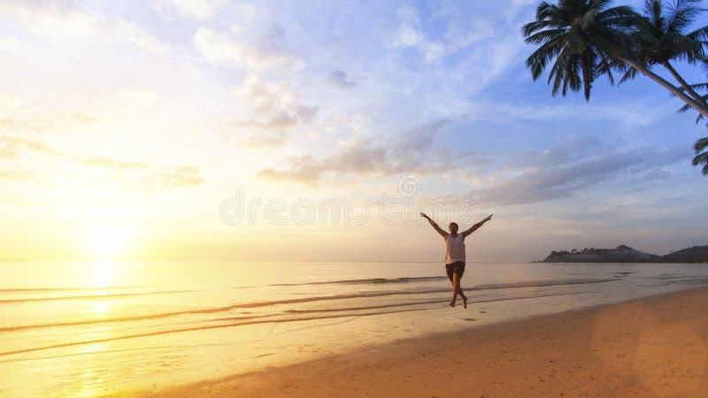 Junger Mann, der glücklich auf den Ozeanstrand springt stockbilder
