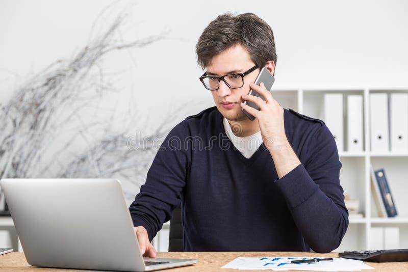 Junger Mann in der Glasfunktion am Schreibtisch lizenzfreies stockbild