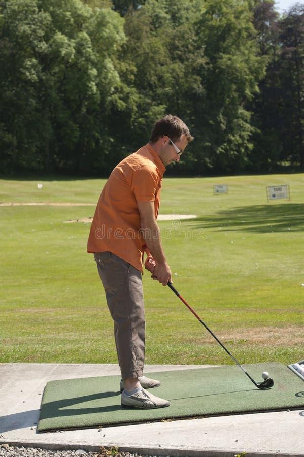 Junger Mann, der Golf an der antreibenden Reichweite erlernt stockfotos