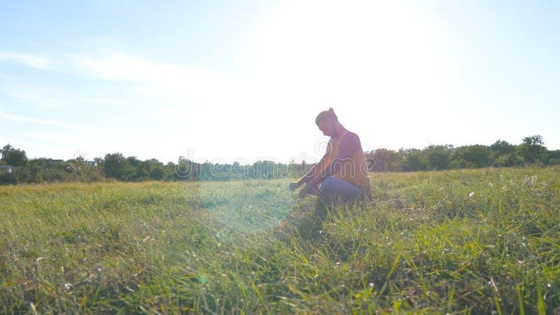 Junger Mann, der am grünen Gras in der Wiese sitzt und Yogaübung tut Muskulöser Kerl, der seinen Körper an der Natur ausdehnt lizenzfreie stockfotografie