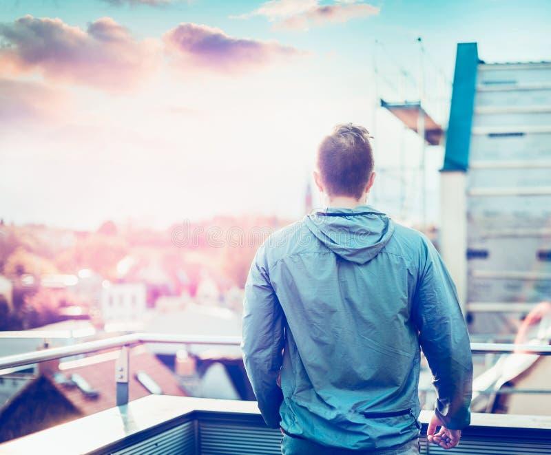 Junger Mann in der grauen Jacke mit dem kurzen Haar, stehend auf dem Balkon des Hauses und bewundert Sonnenuntergang unscharfes S lizenzfreie stockfotos