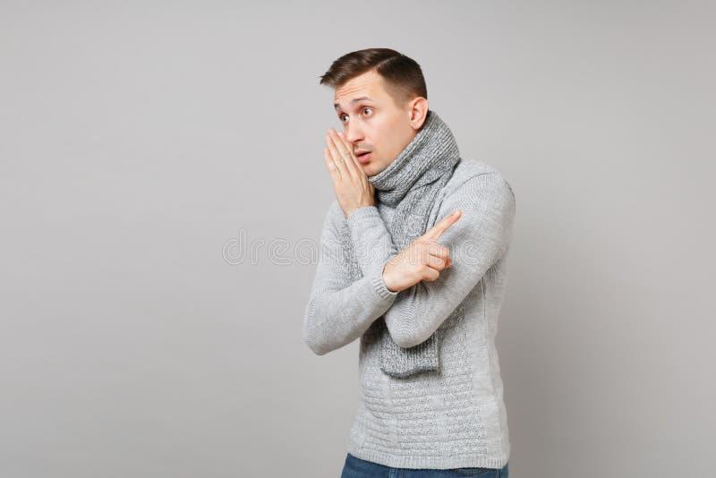 Junger Mann in der grauen Strickjacke, Schal flüstert Klatsch, sagt Geheimnis mit Handzeichen, PunktZeigefinger beiseite an lizenzfreie stockbilder