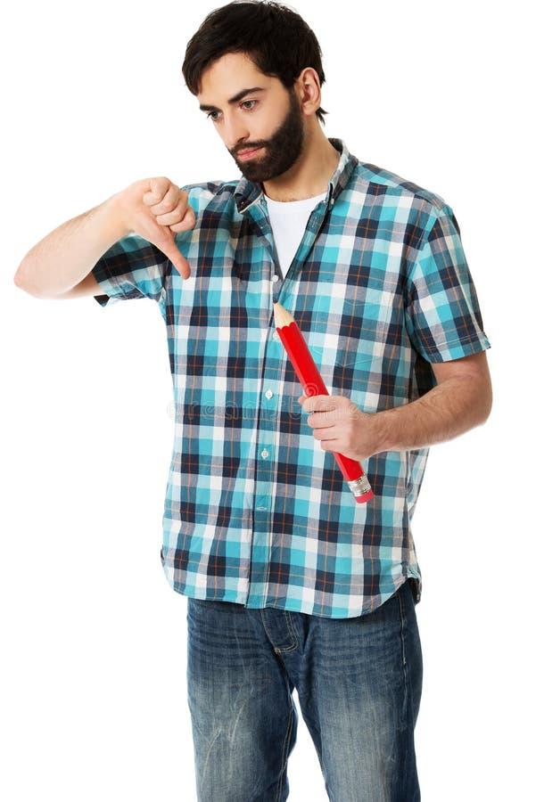 Junger Mann, der großen roten Bleistift hält lizenzfreie stockfotos