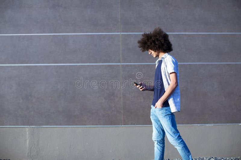 Junger Mann, der Handy auf Straße verwendet lizenzfreies stockfoto