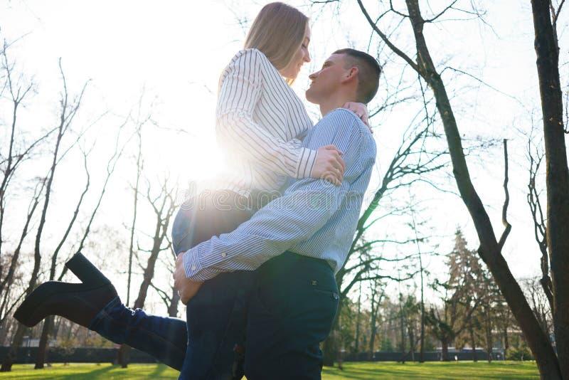 Junger Mann, der herauf seine Freundin am sonnigen Hintergrund anhebt Happine stockbild