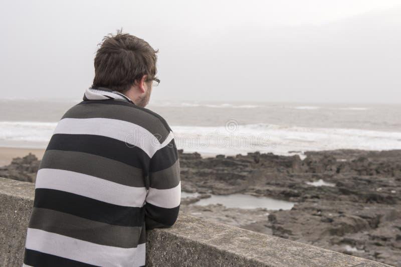 Junger Mann, der heraus über dem Meer an einem windigen Tag schaut stockfotografie