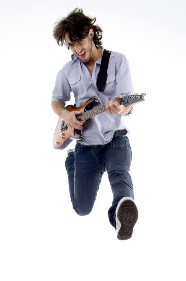 Junger Mann, der hohe Holding seine Gitarre springt lizenzfreies stockbild