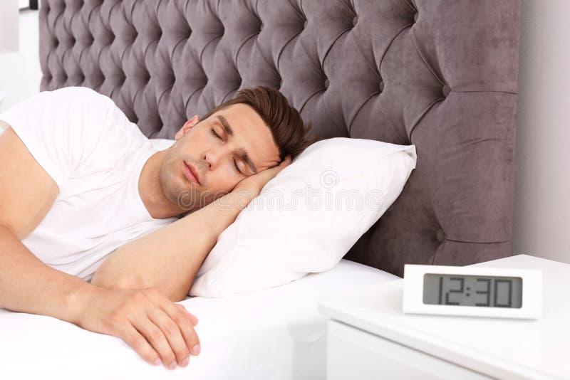 Junger Mann, der im Bett und im elektronischen Wecker auf nightstand schläft lizenzfreies stockfoto