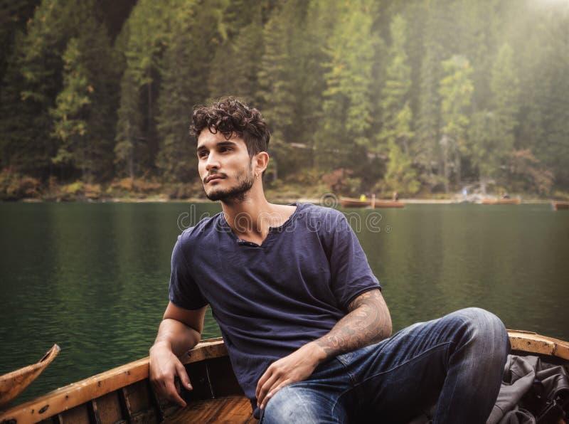 Junger Mann, der im Boot sich entspannt stockfotos