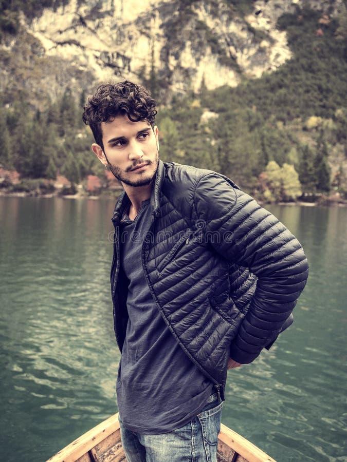 Junger Mann, der im Boot sich entspannt stockfotografie