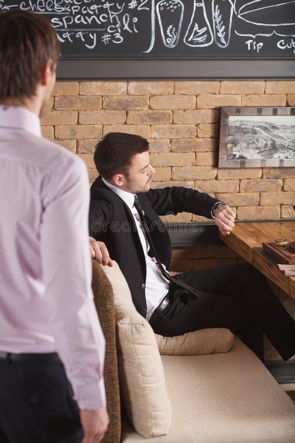 Junger Mann, der im Café wartet auf jemand sitzt stockfotos
