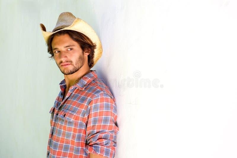 Junger Mann, der im Cowboyhut ernst schaut lizenzfreie stockfotos